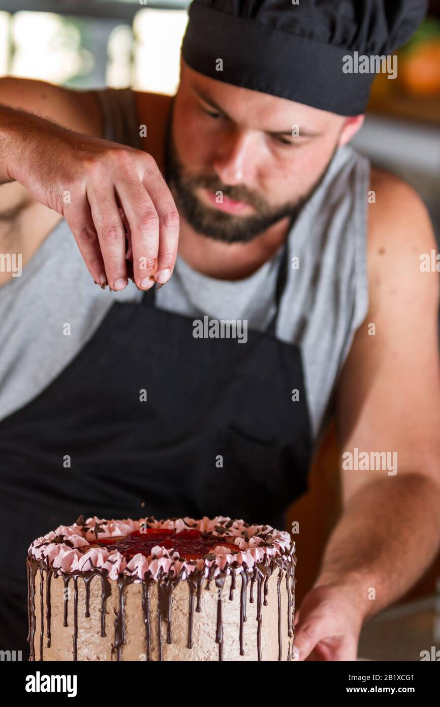 Fine Male Baker Decorating A Chocolate Birthday Cake With Strawberry Funny Birthday Cards Online Overcheapnameinfo