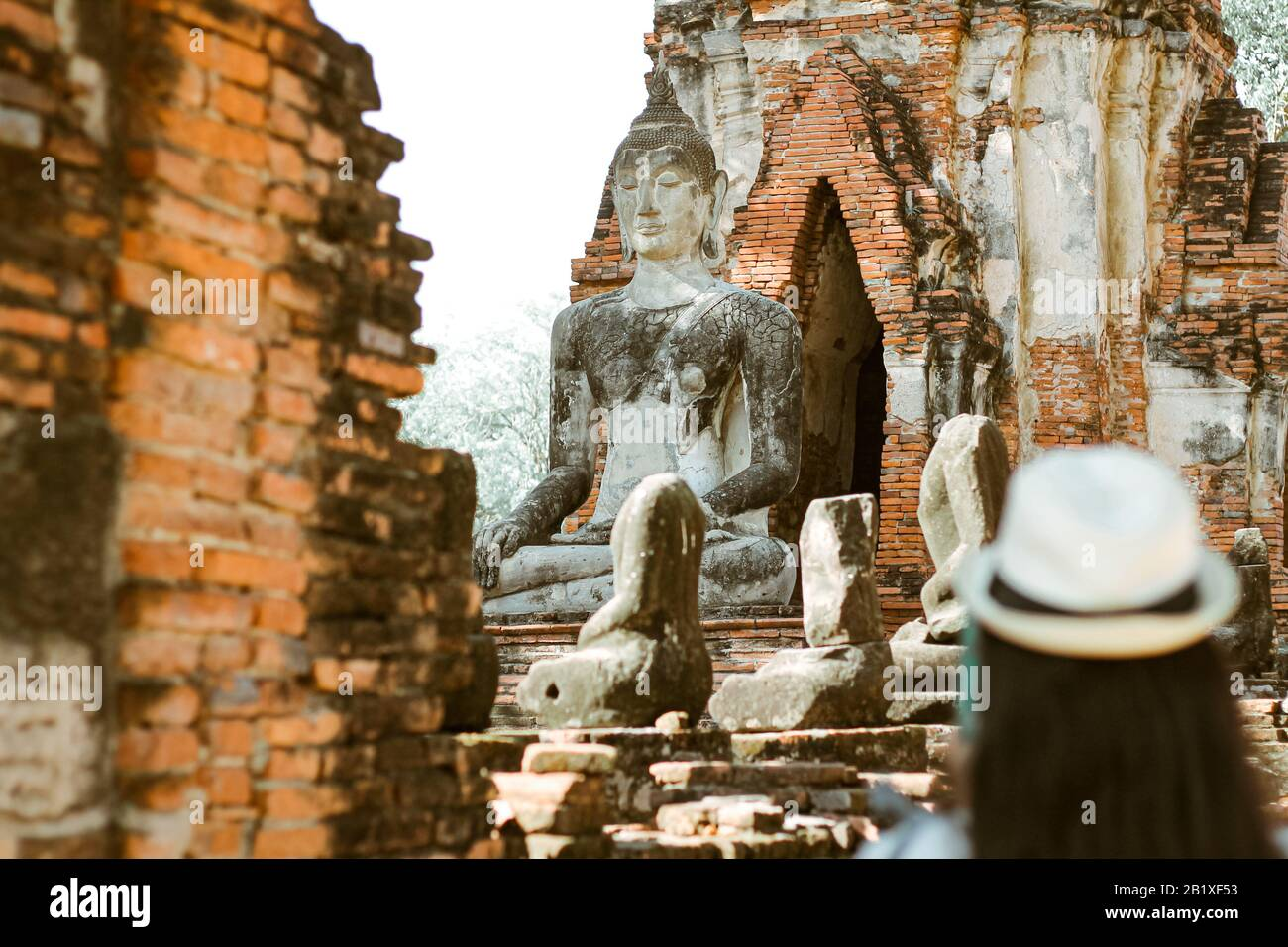 A tourist exploring Ayutthaya Historical Park (focus on the background) which is one of the famous cultural travel destination in Thailand Stock Photo