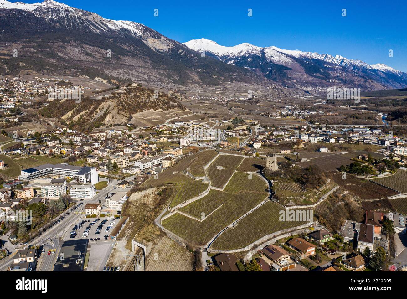 Aerial view of the city of Sierre in Canton Valais with vineyars, and a castle and medieval tower overlooking the Rhone valley in Switzerland on a sun Stock Photo