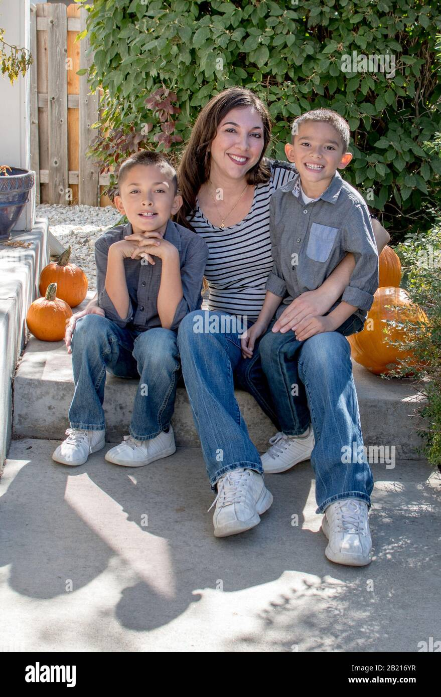 A single mom poses with her two boys in this beautiful Autumn outdoor portrait Stock Photo
