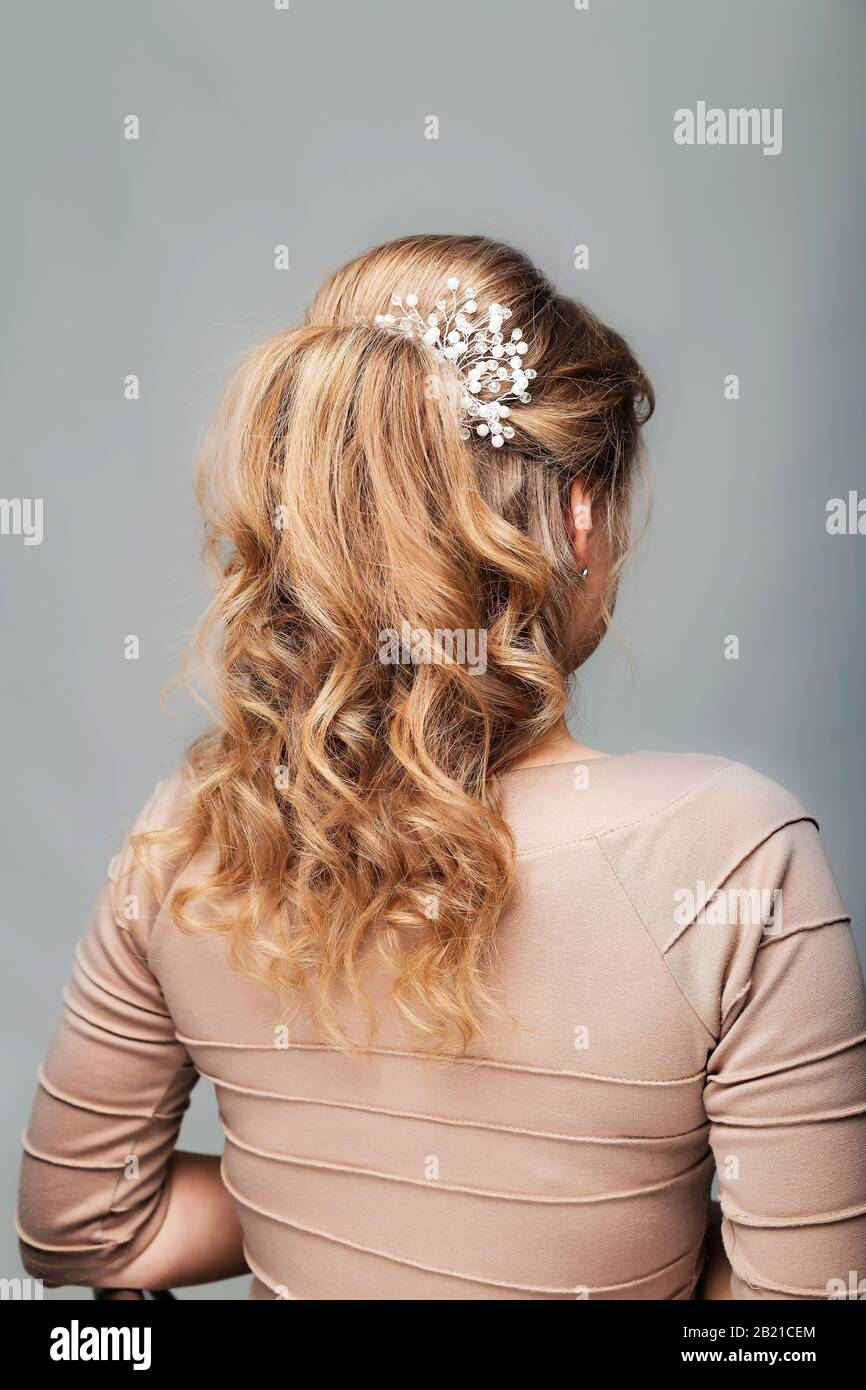 Wave curls hairstyle. Hairstyle on blond hair woman with long hair on a white background. Professional hairdressing services.Hair styling, making Stock Photo