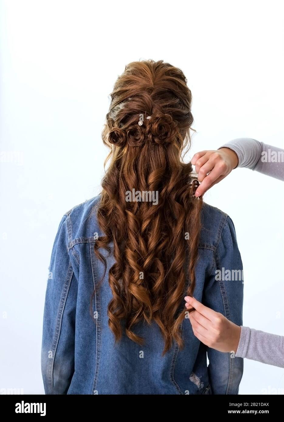 Wave curls hairstyle. Hairdresser making hairstyle to red brown hair woman with long hair using comb on white background. Professional hairdressing Stock Photo