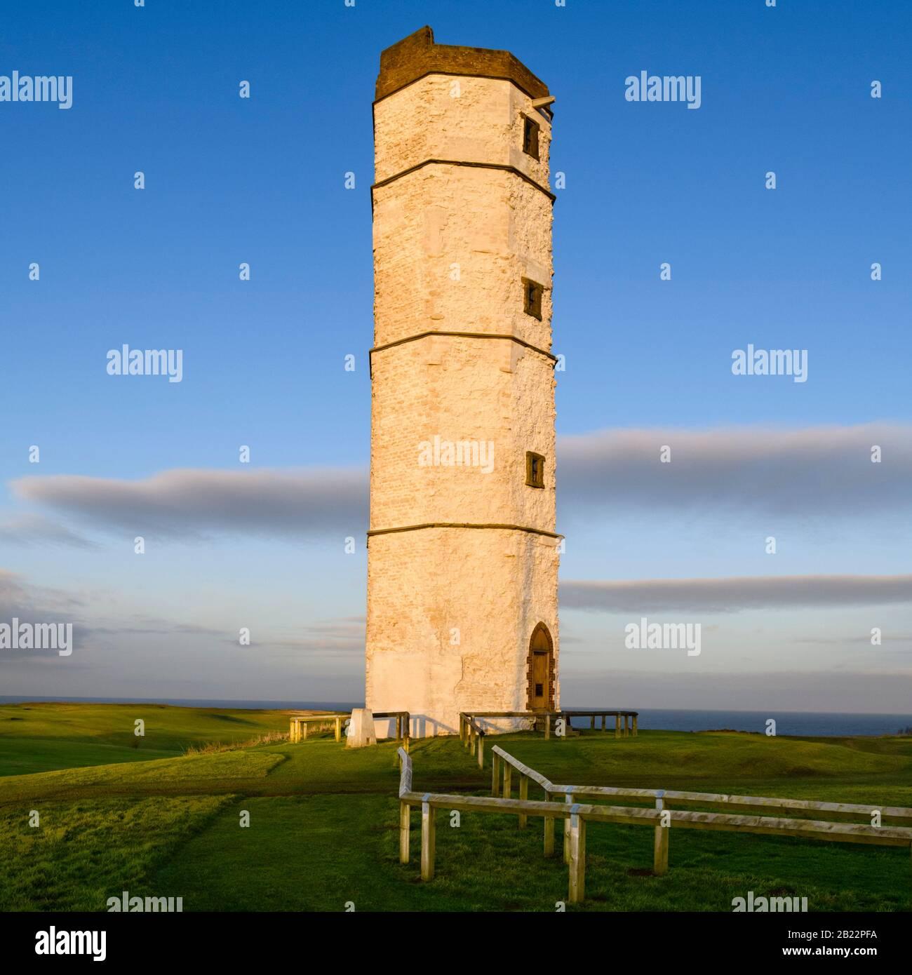 Exterior of old sunlit Flamborough Head Lighthouse (historic tall white chalk octagonal beacon tower) & deep blue sky - near Bridlington, England, UK. Stock Photo
