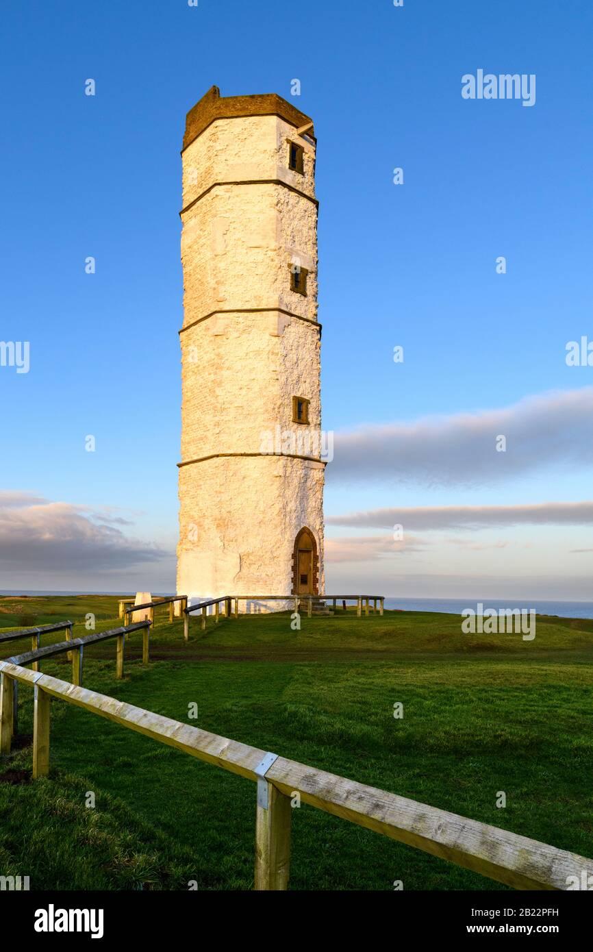Exterior of old sunlit Flamborough Head Lighthouse (historic tall white chalk octagonal beacon tower) & deep blue sky - Yorkshire Coast, England, UK. Stock Photo