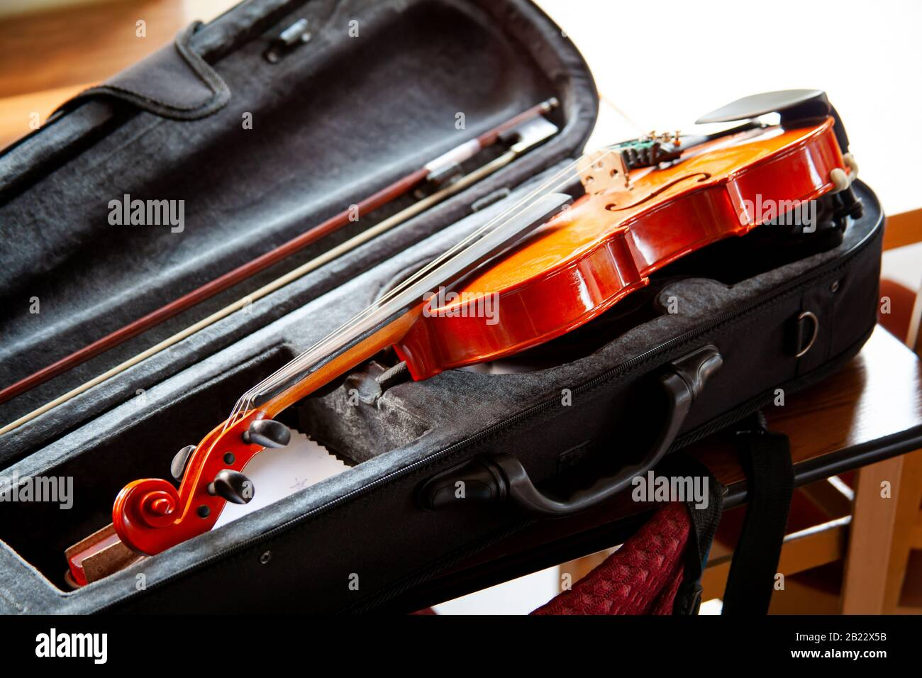 Violin with a bow laying in an open black fiddle case on the table. Classical musical string instruments group concept, nobody. Safe instrument Stock Photo