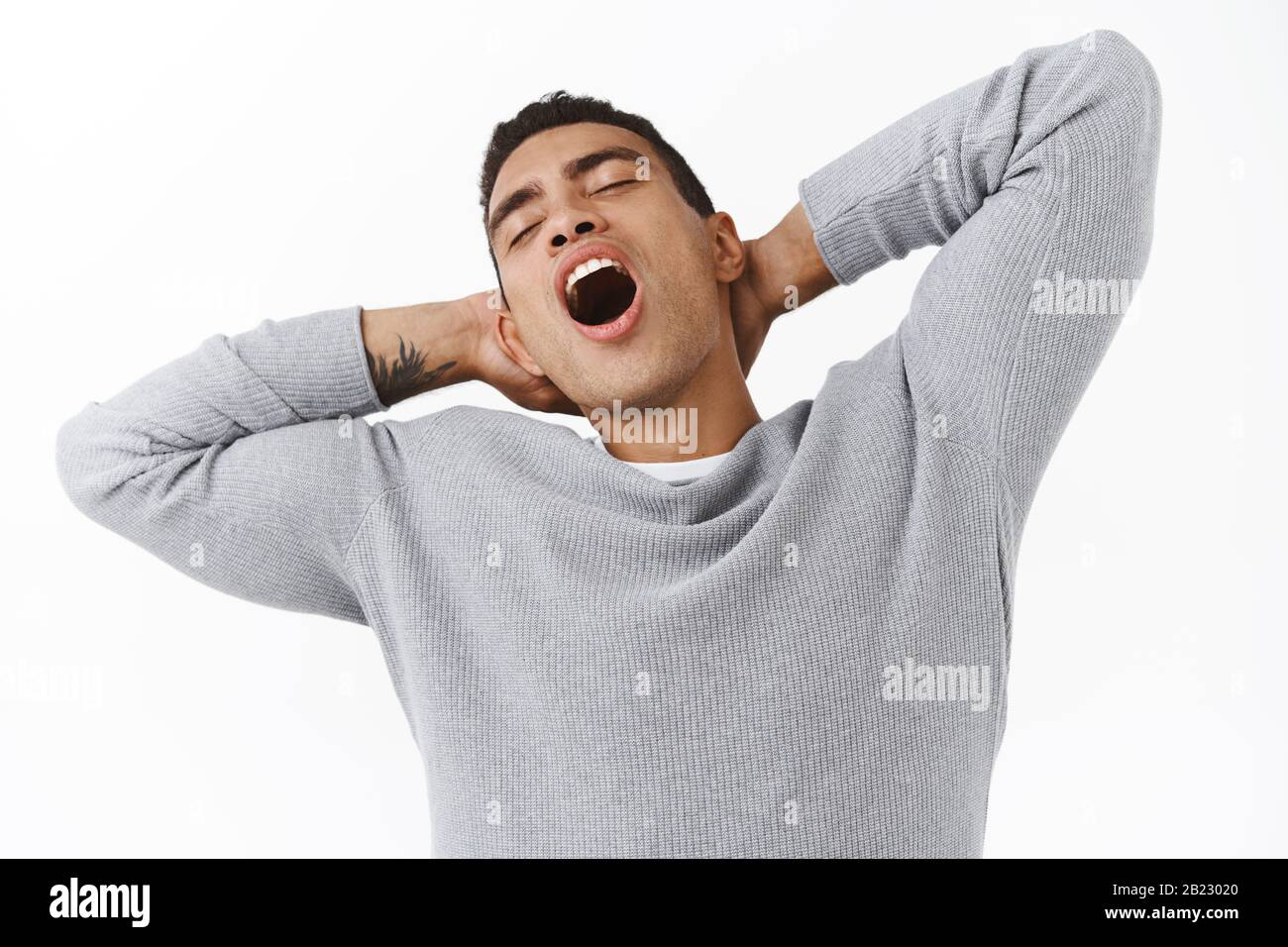 Close-up lazy handsome young hispanic guy with athletic body, stretching and holding hands behind head, yawning with closed eyes tired, feeling sleepy Stock Photo
