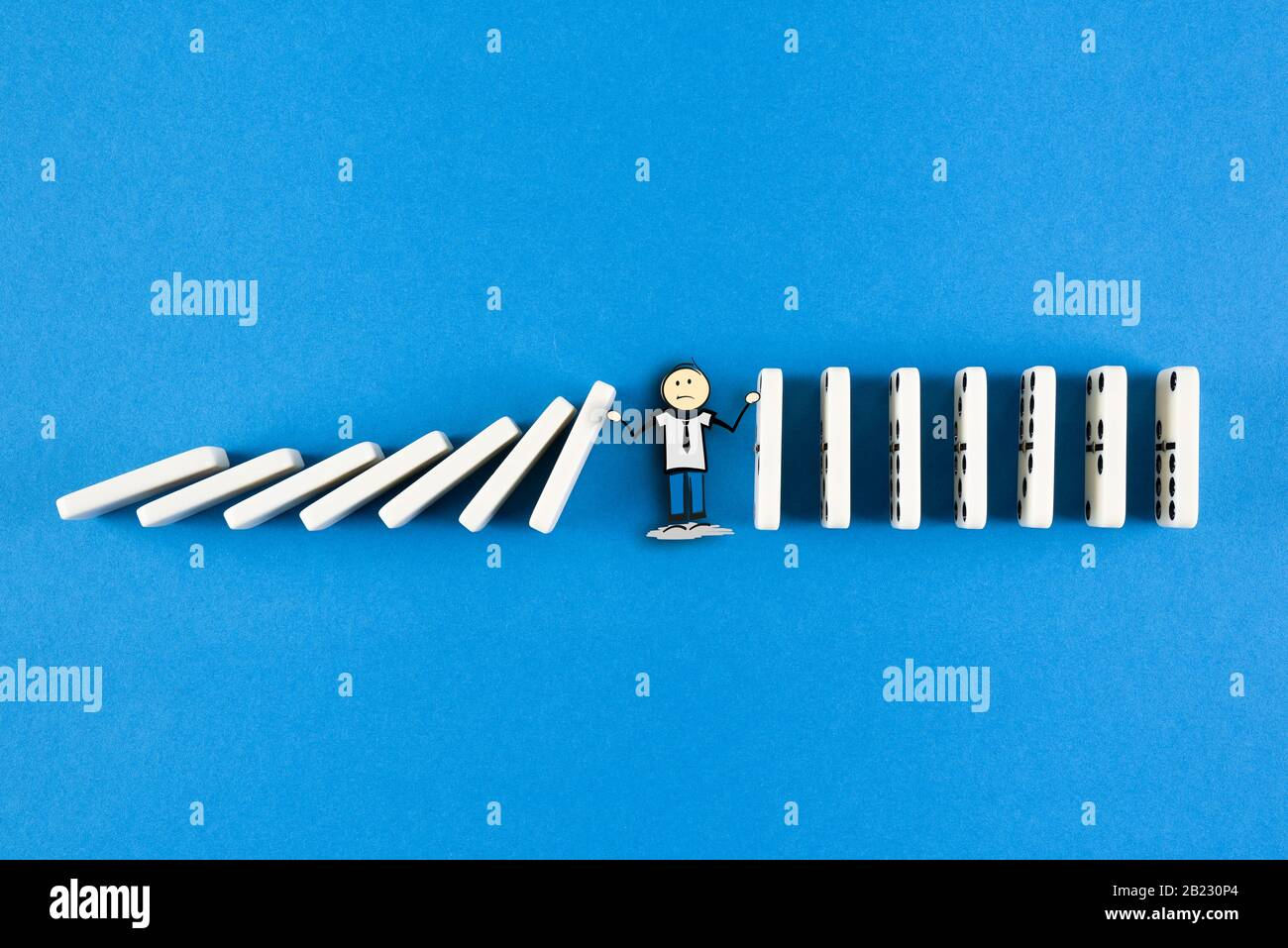 stickman figure preventing line of domino tiles from falling, domino effect and event chain concept Stock Photo