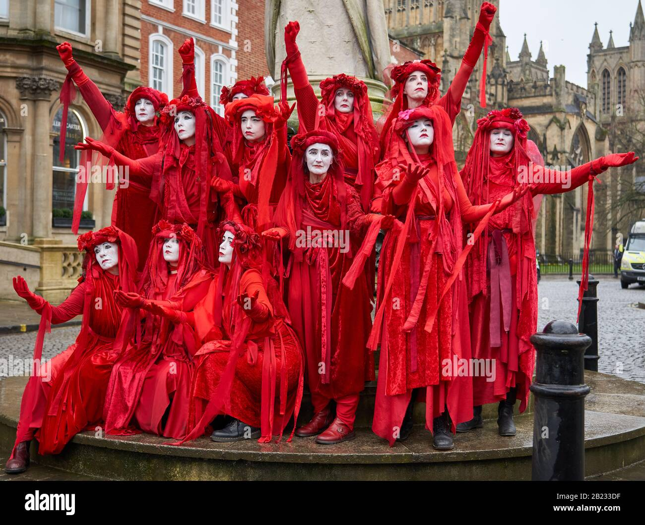 The Red Brigade of Extinction Rebellion displaying their striking poses in peaceful protest supporting action on climate change - Bristol UK Stock Photo