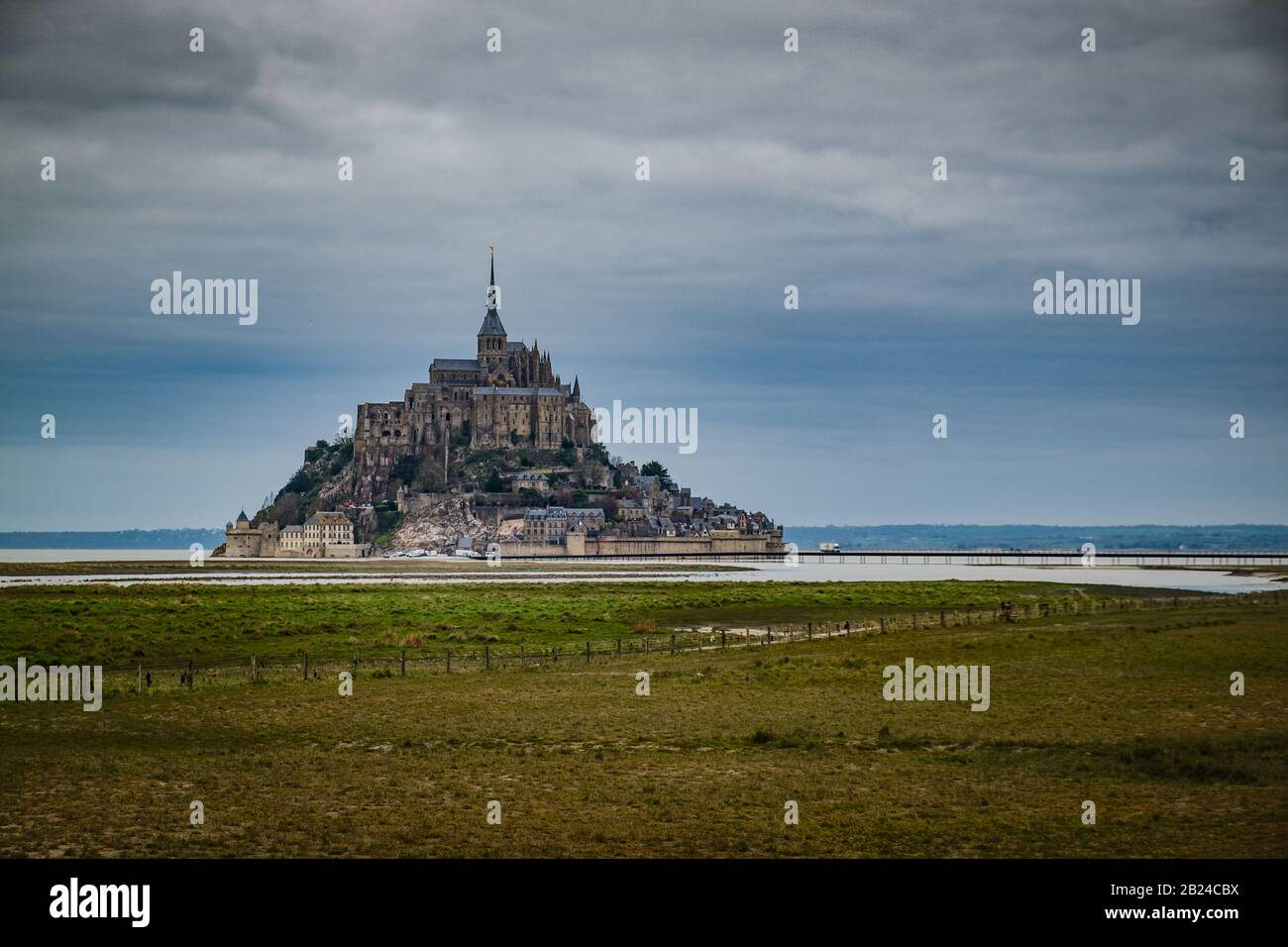 View of famous Le Mont Saint-Michel tidal island. Green field in the foreground Stock Photo