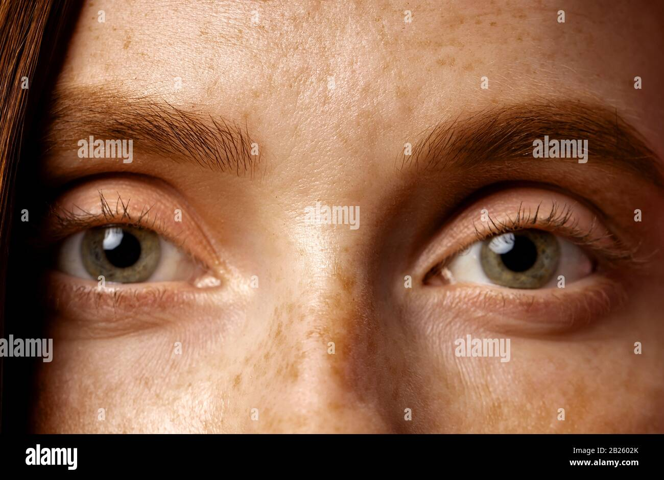 Beautiful female eyes. Close up cropped shot of redhead caucasian young woman with freckles, no makeup. Ophthalmology, vision concept. Stock Photo