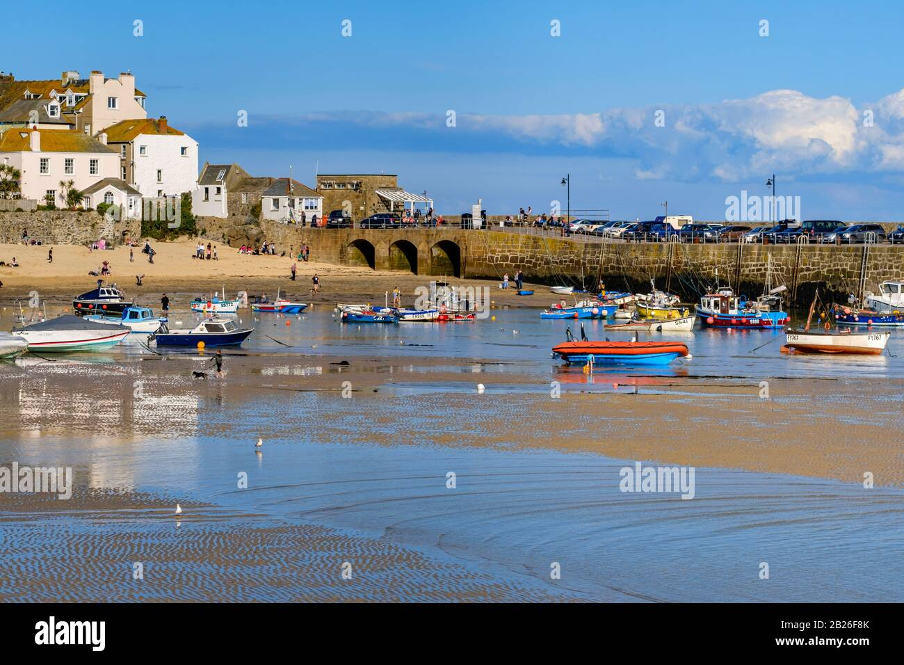 Harbour beach to the Harbour at St Ives with houses and Smeatons Pier in the distance, people on the beach and fishing boats moored ,Cornwall, S West Stock Photo