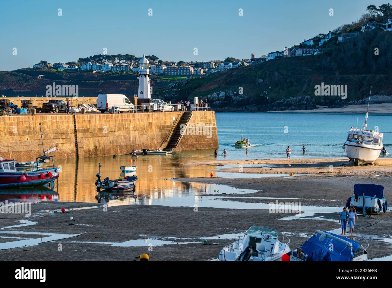 St Ives Harbour beach, with boats in the harbour with Smeatons Pier and St Ives new lighthouse, blue skies, blue sea, Cornwall, South West, UK Stock Photo