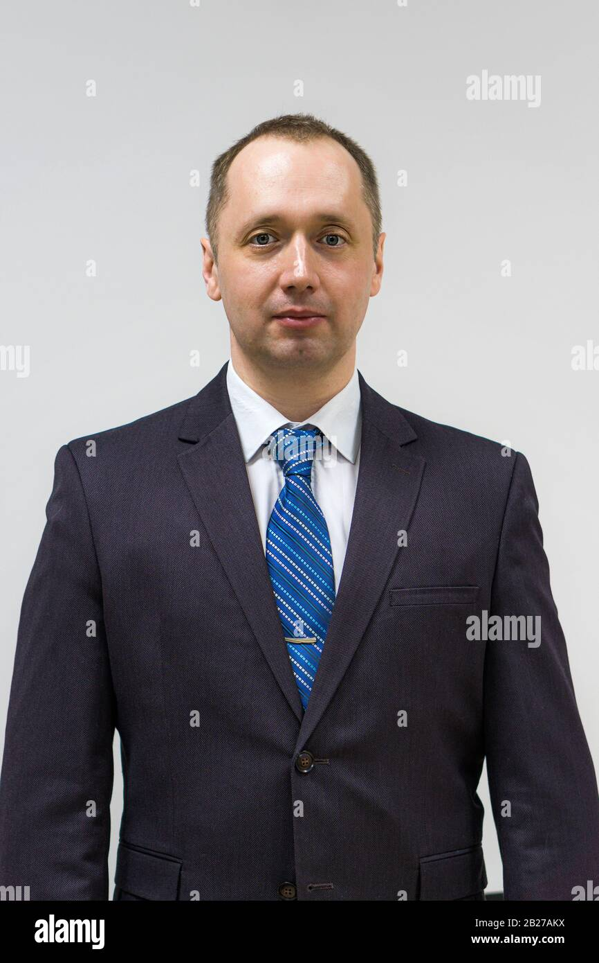 portrait of a confident, purposeful, successful businessman weared in grey suit and blue neck tie Stock Photo