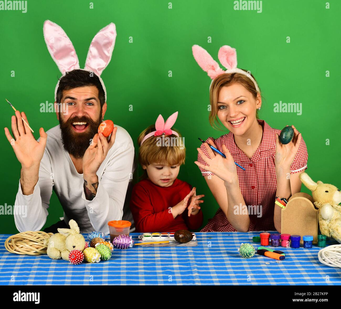 Mother, father and son painting eggs in pink bunny ears. Happy moments and Easter celebration concept. Family members preparing for Easter on green background. Man and woman with happy smiles. Stock Photo
