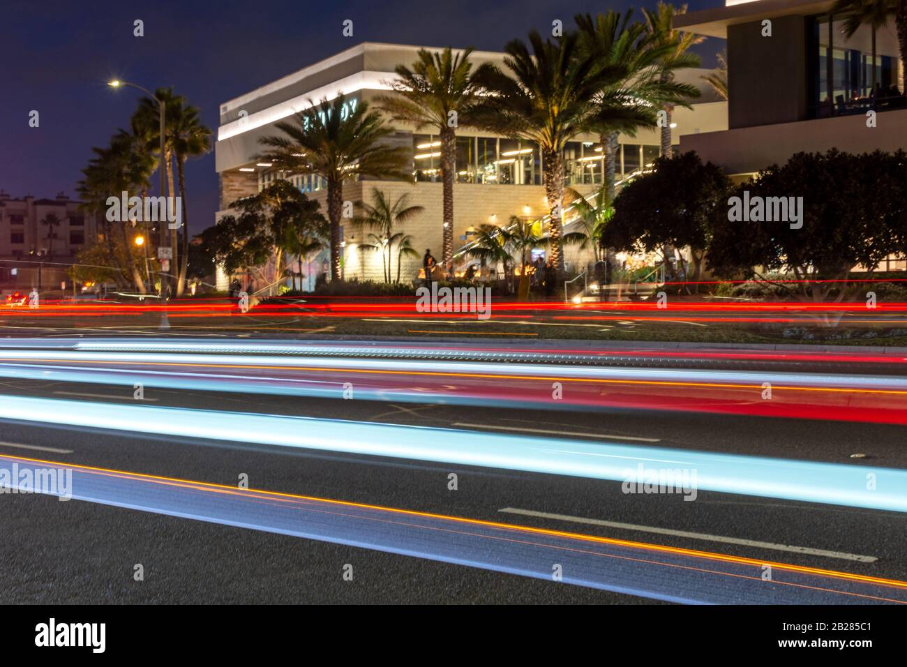Colorful light trails on a city road in front of illuminated buildings at night. Stock Photo