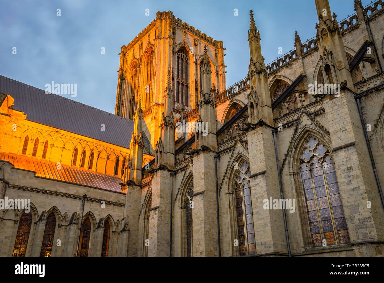 A  illuminated section of York Minster with its medieval gothic architecture and central tower at dawn.  Stained glass windows are lit. Stock Photo
