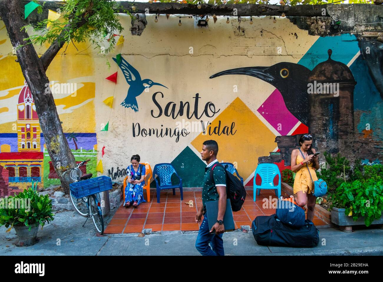 A female tourist stands by a colorful wall in the Getsamaní district, Cartagena, Colombia Stock Photo