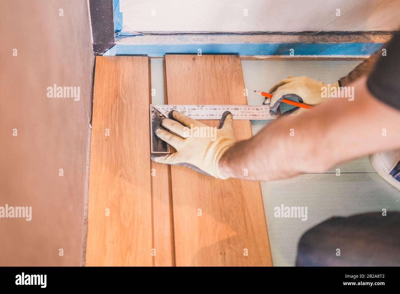 Worker measuring and marking laminate for cutting - installing floating floor - close-up on hands - home renovation concept Stock Photo