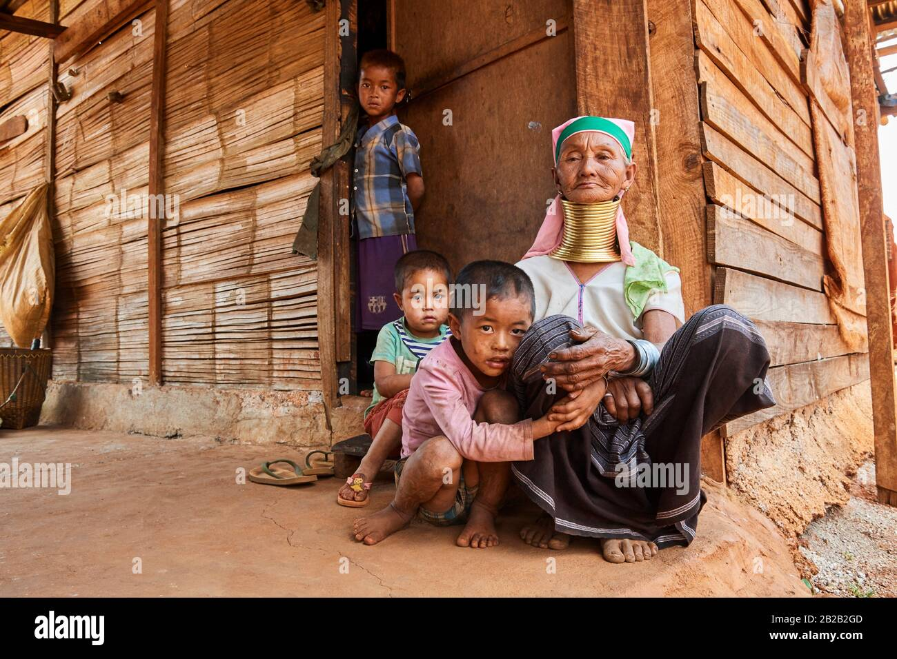 Kayan Lahwi woman with brass neck coils and traditional clothing looking after her grandchildren while the parents are working in the farm. The Long Stock Photo