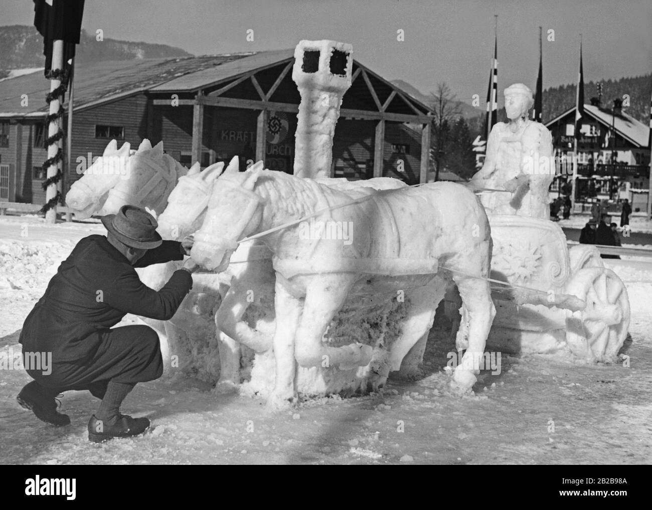"""On the occasion of the Winter Olympics in Garmisch-Partenkirchen an artist created a """"Roman Quadriga"""" snow sculpture. In the background, the K.D.F. Festhalle. Stock Photo"""