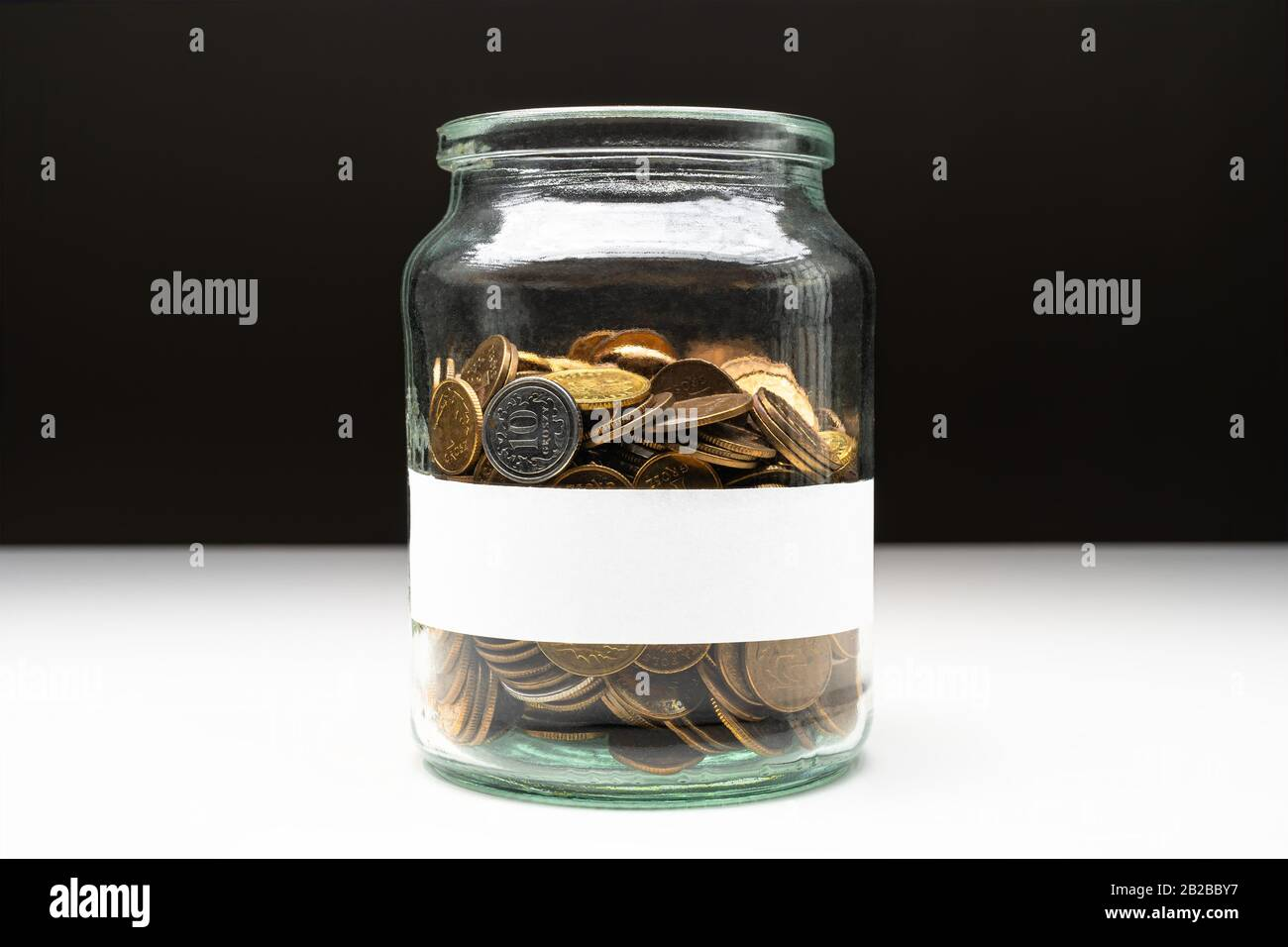 Coins in a jar with blank white label. Savings abstract concept. Copy space. Stock Photo