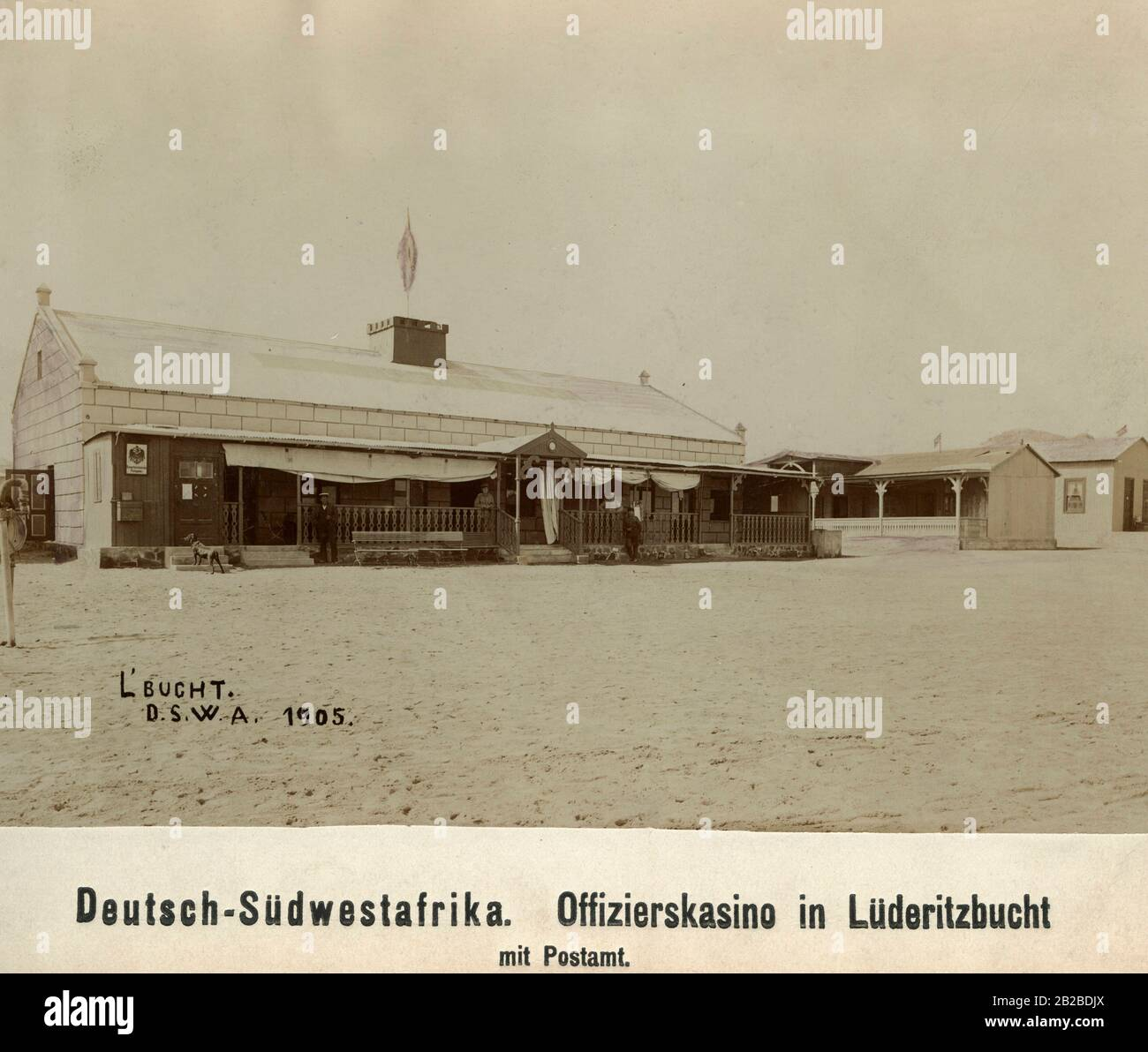 German men in uniform standing in front of the officers' casino in Luderitz Bay, German South West Africa. A sub-post office is integrated in the casino. Stock Photo