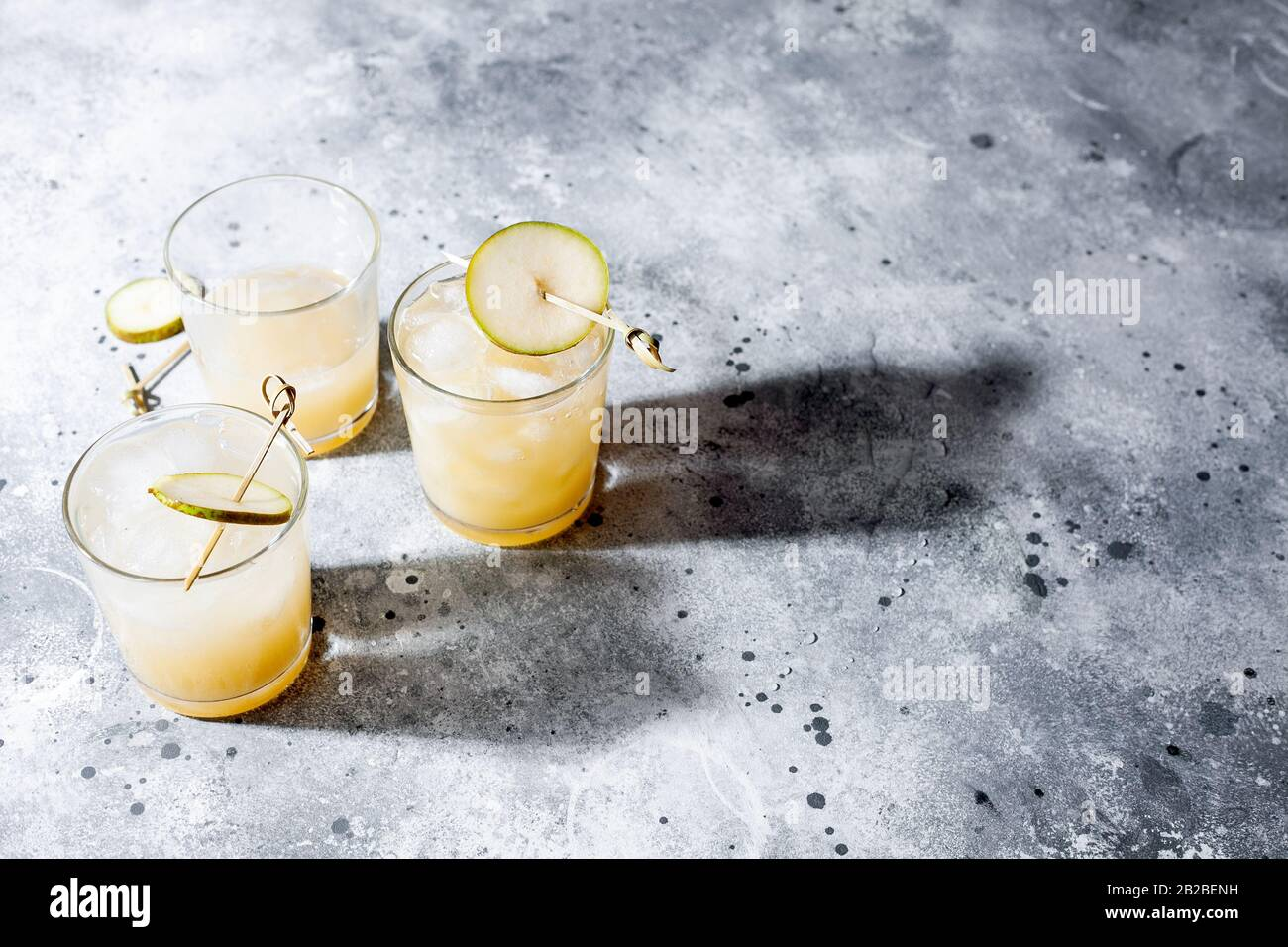 Cold pear cocktail or mocktail with soda and pear puree and fruit slices in short glass on gray background with shadow. Refreshing summer drink Stock Photo