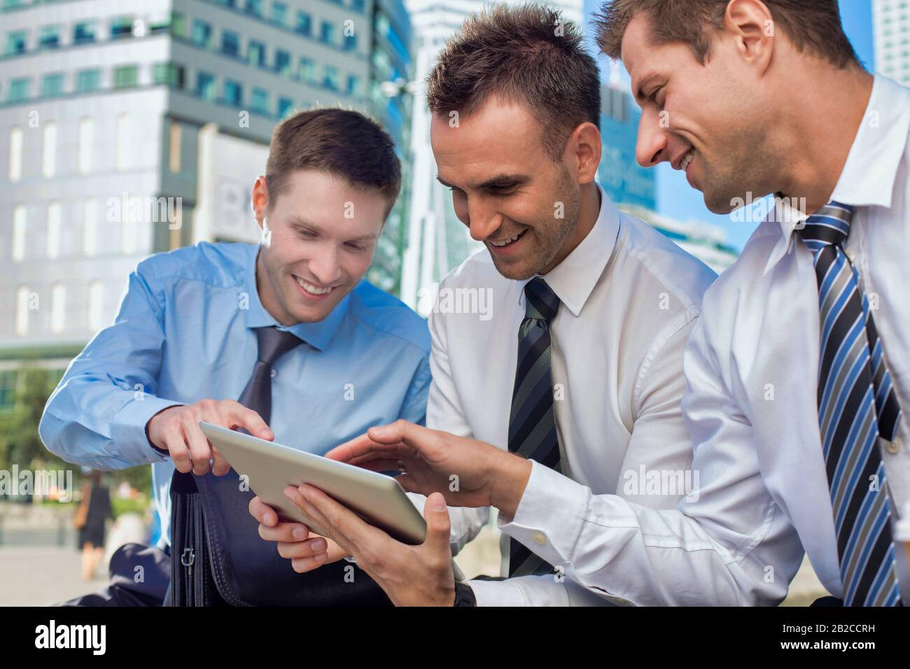 Portrait of handsome businessman showing business plan to the other businessman over digital tablet while sitting Stock Photo