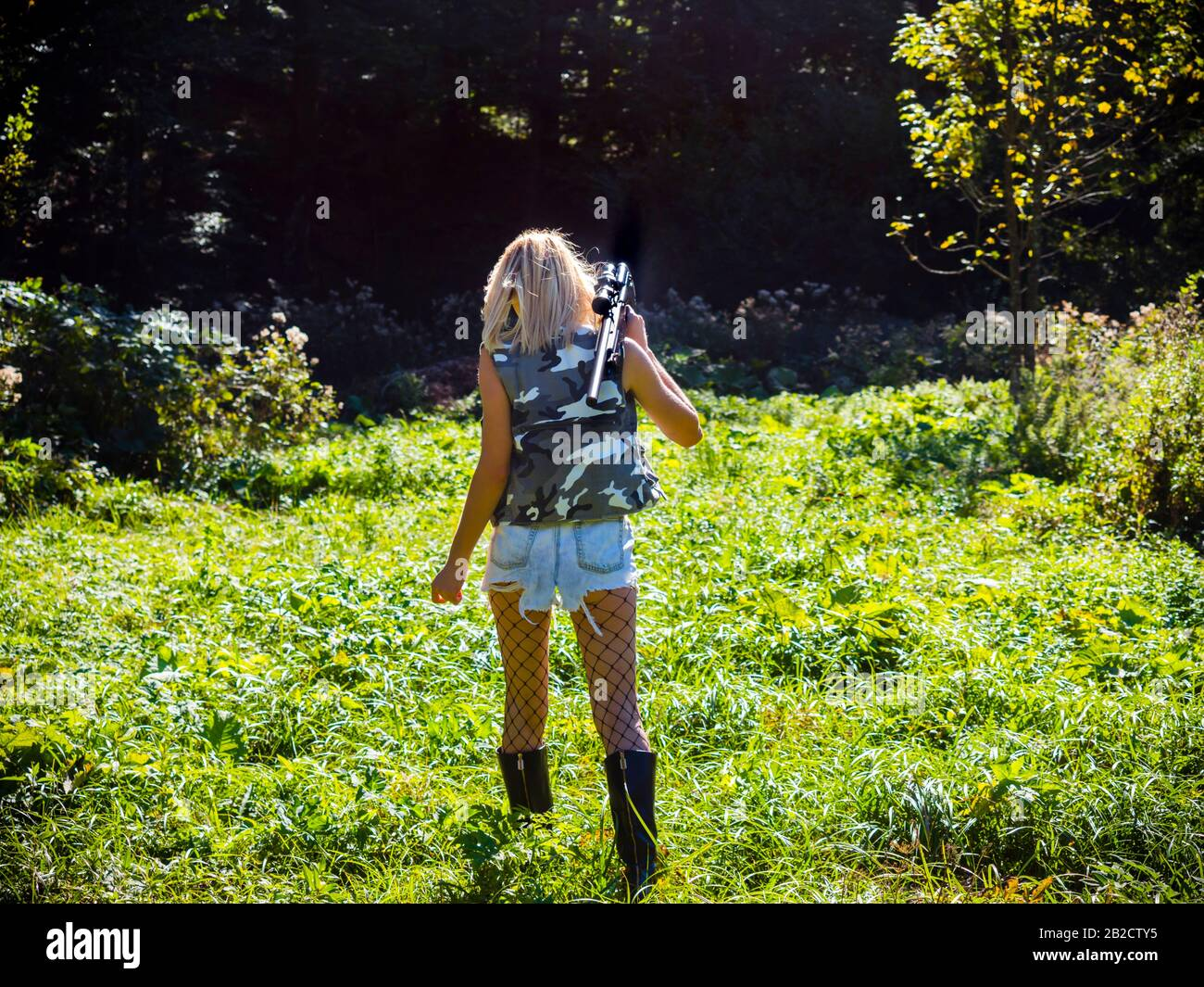 Attractive blonde female aka sharpshooter walking towards dark Green forest hands holding rifle on her shoulder view from back behind rear rearview Stock Photo