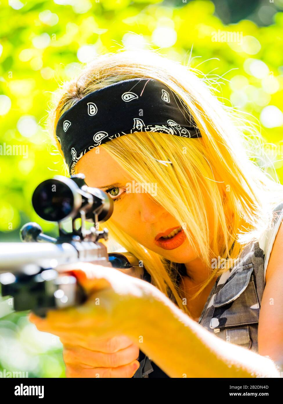 Young blonde woman female sharpshooter with riffle in hands Stock Photo