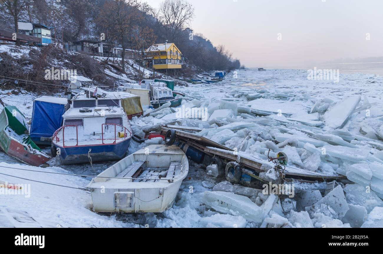 Destroyed boats on a frozen Danube river with lots of ice cubes near Belgrade, Zemun, Serbia Stock Photo