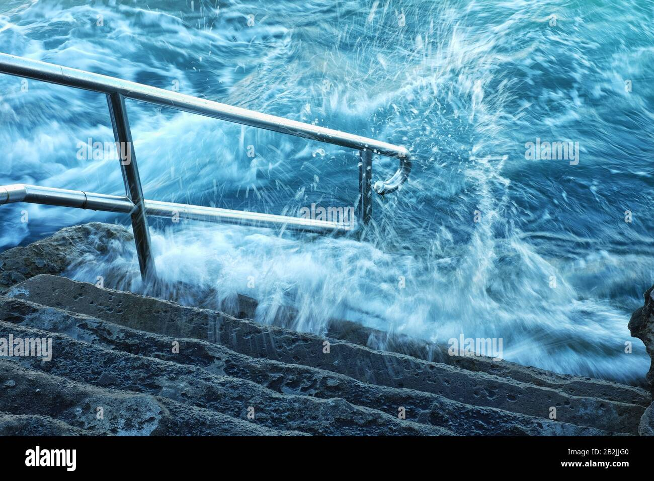 Ocean white water splashes, foams and surges over the steps and handrail of Giles Bathes, ocean rock pool Coogee Bay, Sydney, Australia Stock Photo