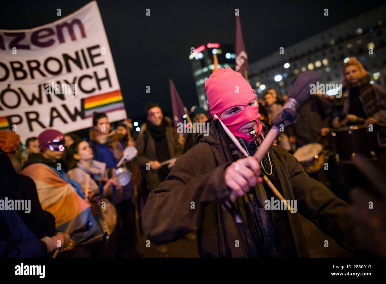 """A masked activist whistling while playing drums during the protest.Dozens of LGBTQ activists and citizens protested in Warsaw against the LGBT - free zones resolutions. A third of Poland has officially declared itself an """"LGBT-free"""" zone as local governments adopt resolutions against """"LGBT propaganda."""" Nearly 100 Polish municipal or local governments across an area larger than the size of Hungary have now proclaimed themselves to be """"free from LGBT ideology,"""" and have adopted resolutions that officially enable intolerance and discrimination against LGBTQ people. Stock Photo"""