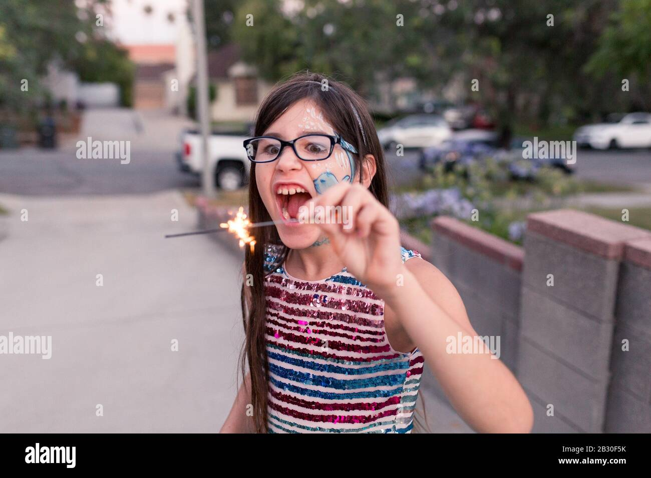 Kids are playing with sparkers on their driveway in the city on the 4th of July. Stock Photo