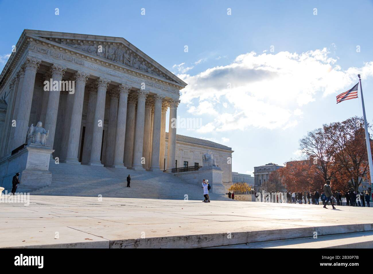 United States Supreme Court on sunny day in D.C. with the USA flag waving in the sunlight. Stock Photo