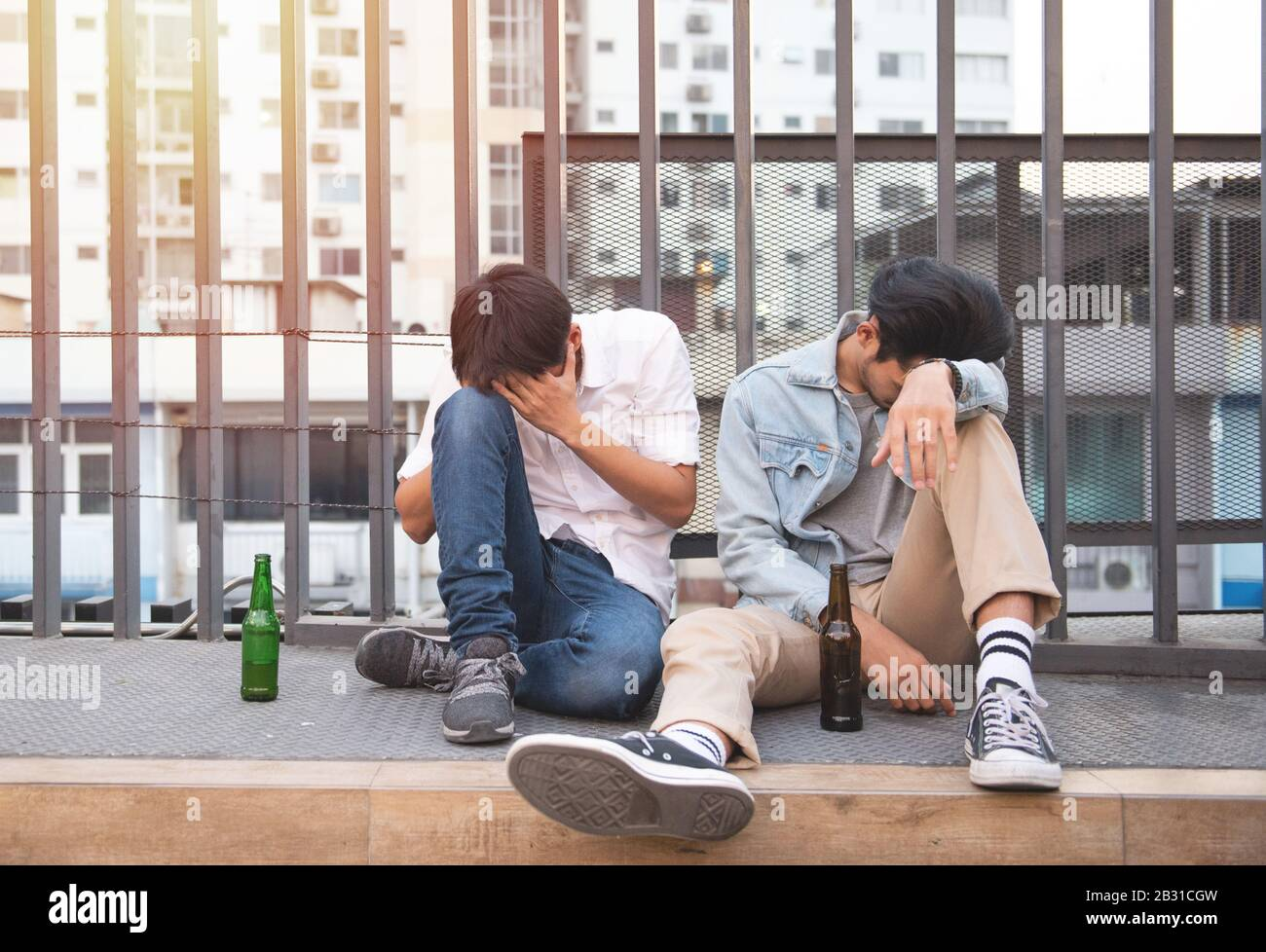 Two young men drunk and sit sleeping on street with bottle of beer in unhappy. Stock Photo