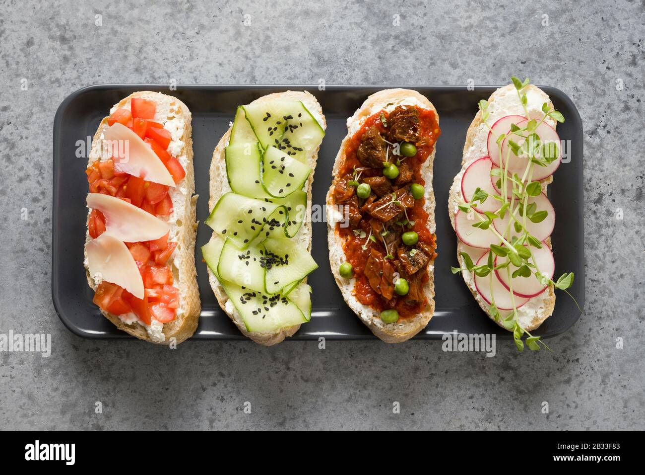 Sandwiches on ciabatta toast with fresh vegetables, radishes, tomatoes, cucumbers and microgreens on gray background. View from above. Stock Photo