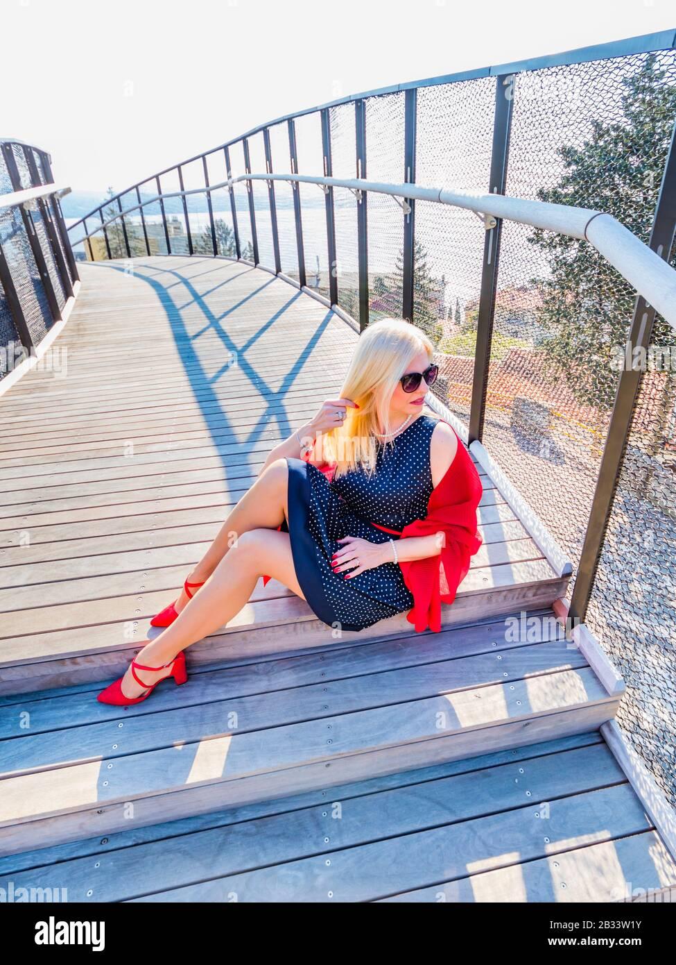 Blonde woman sitting on wooden foot-bridge footbridge Stock Photo
