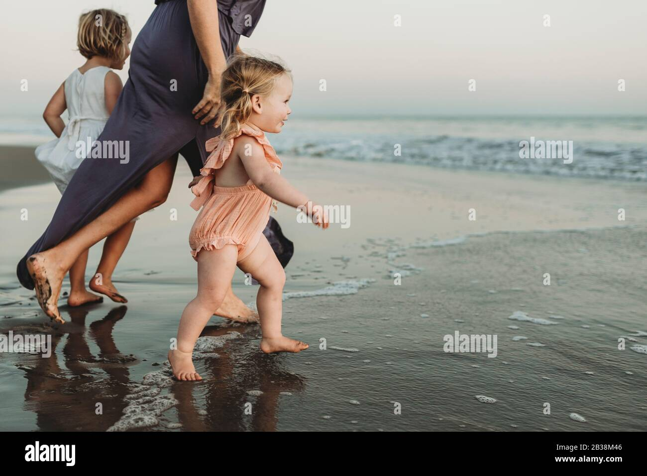 Side view of toddler girl running into the ocean at sunset Stock Photo