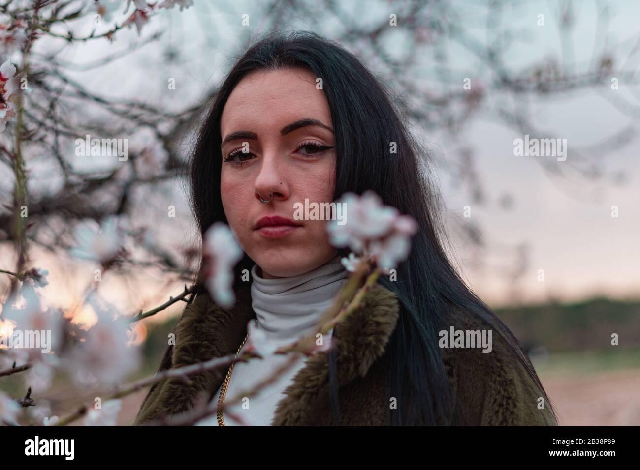 Retrato de mujer con flores y fondo atardeciendo Stock Photo