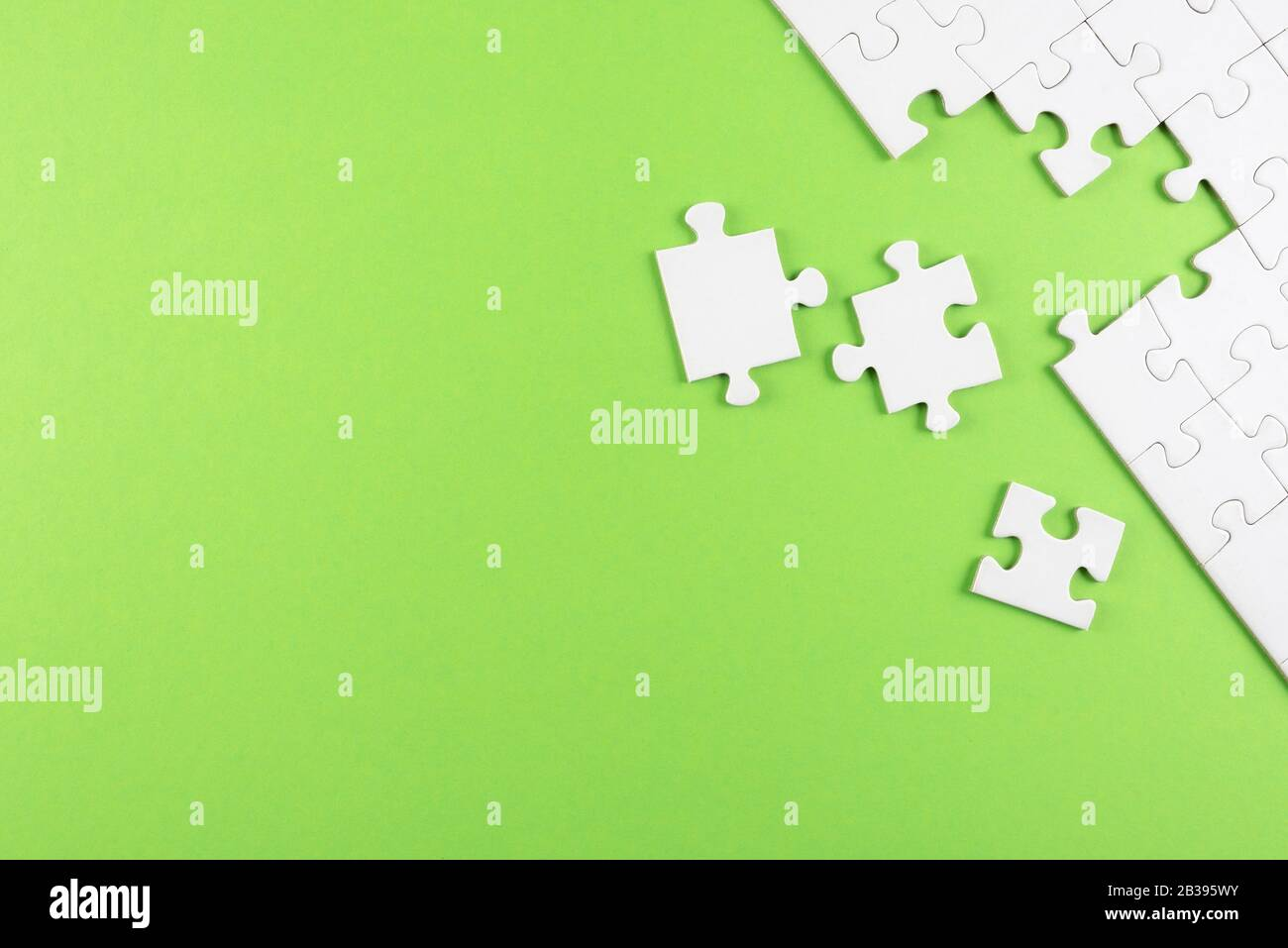 top view of white blank unfinished jigsaw puzzle on green background, completing a task or solving a problem concept Stock Photo