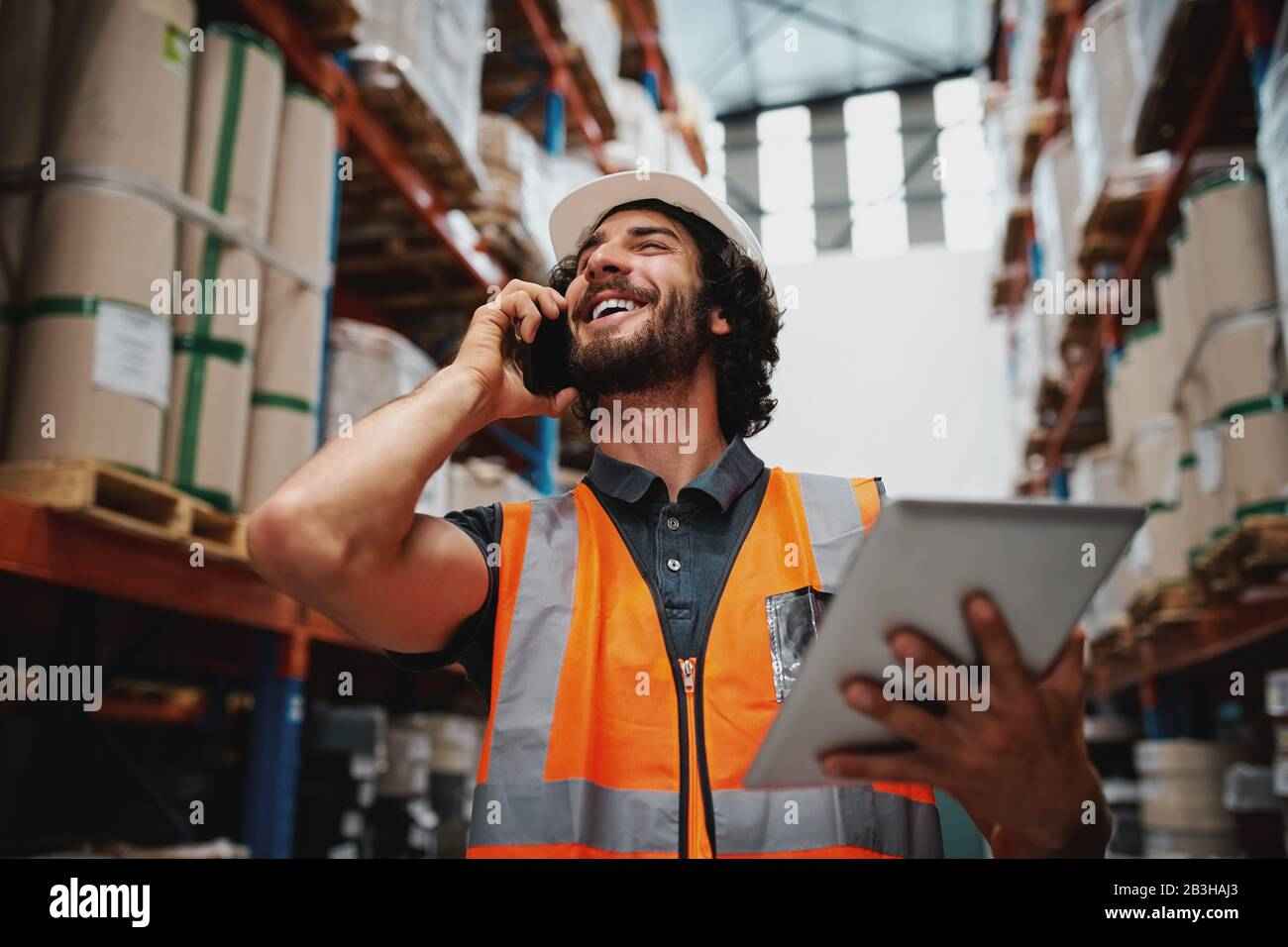 Low angle view of cheerful warehouse supervisor using phone for communication holding digital tablet wearing hardhat and safety vest Stock Photo