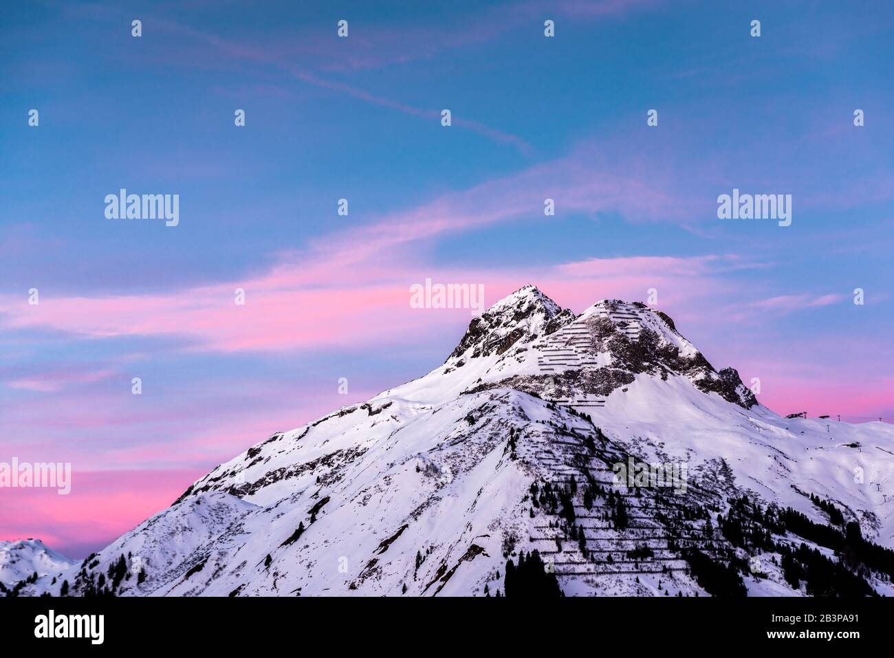 Pink clouds lie in a blue sky above a snowy alpine mountain peak. Stock Photo