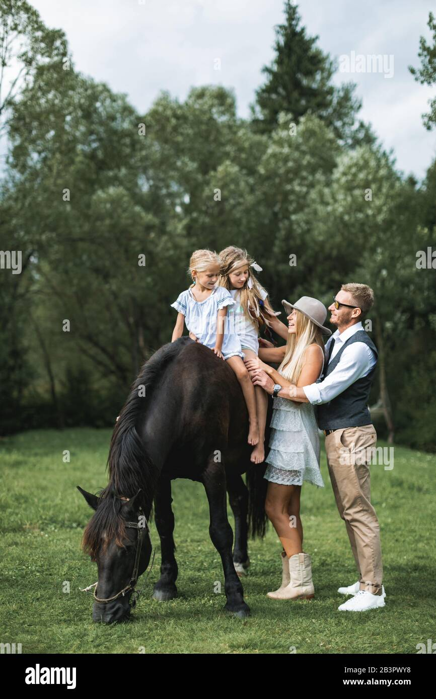 Young Stylish Family In Cowboy Wear Father Mother Teaching Their Two Little Daughters To Ride A Horse Family Horse Riding On The Nature In Stock Photo Alamy