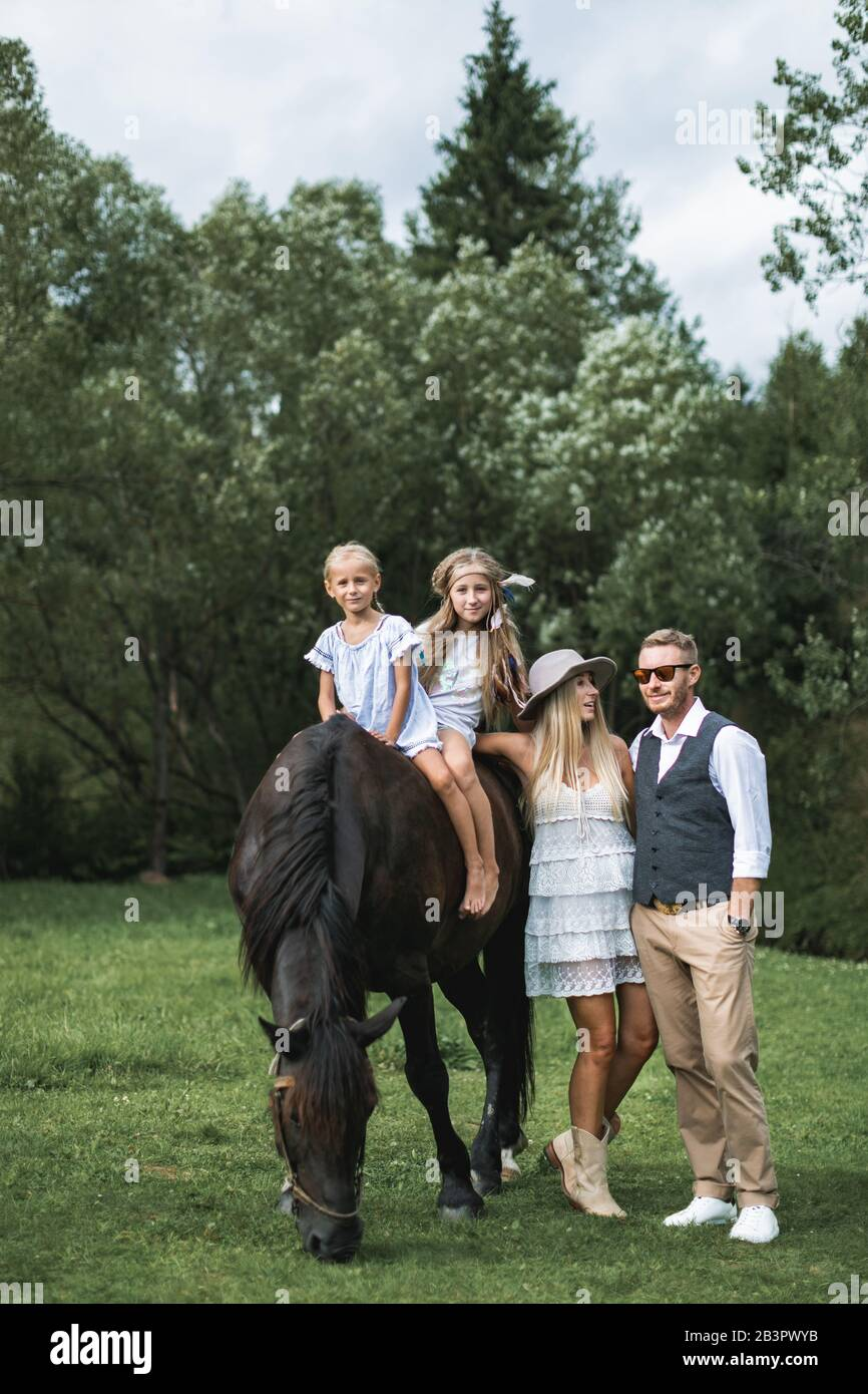 Family Walk Horse Riding Concept Two Little Girls Riding A Brown Horse While Young Stylish Parents In Casual Cowboy Wear Standing Near Horse And Stock Photo Alamy