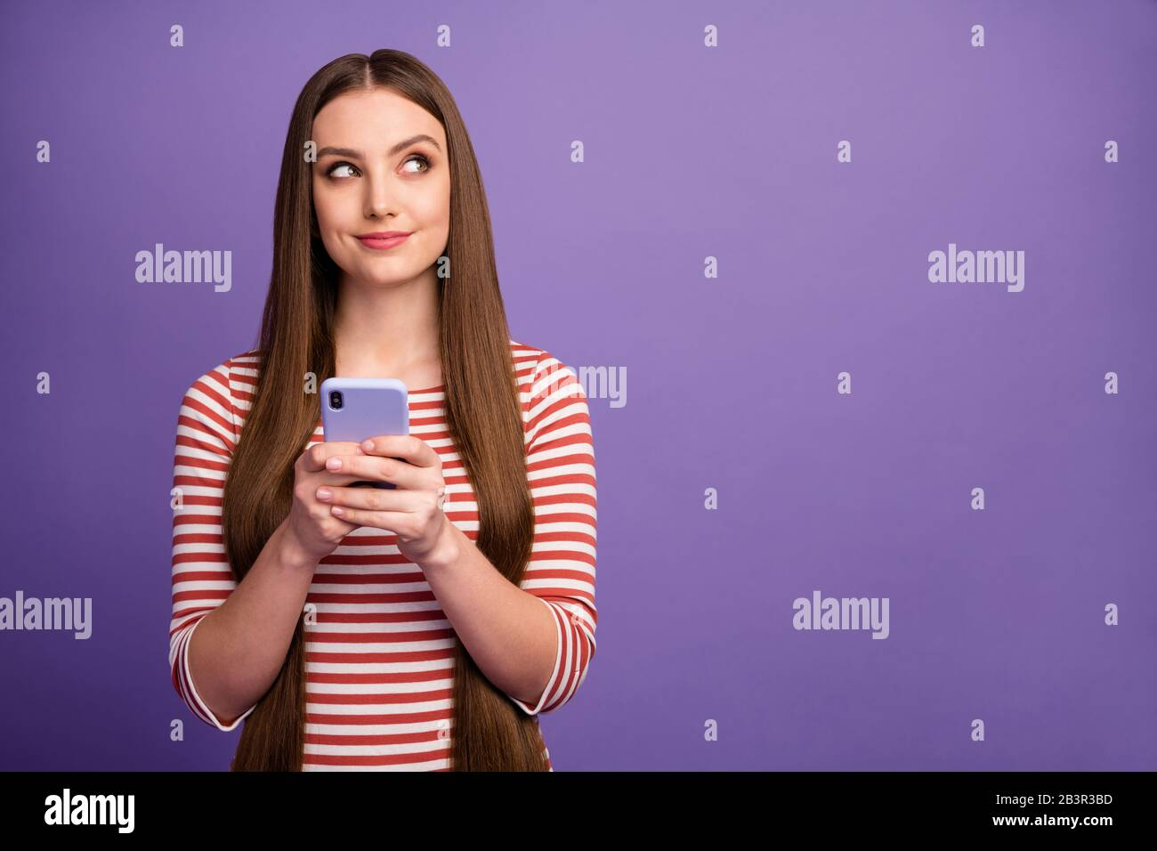 Portrait of minded cute sweet girl look copyspace use smartphone wonder consider blog post subjects wear jumper isolated over purple color background Stock Photo