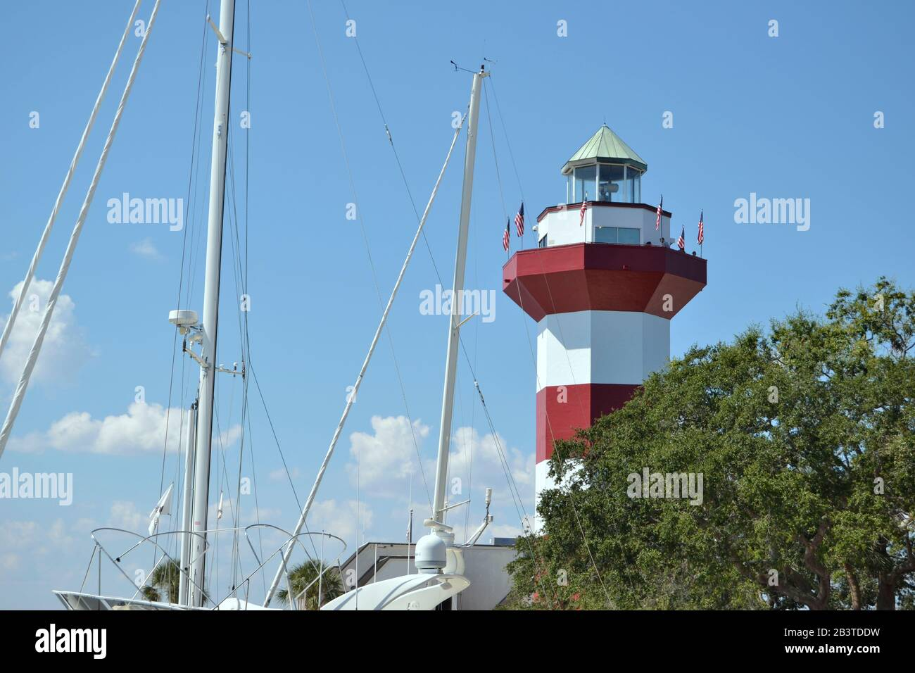 Lighthouse behind trees and with yachts in Harbor Town, Hilton Head Island. Stock Photo