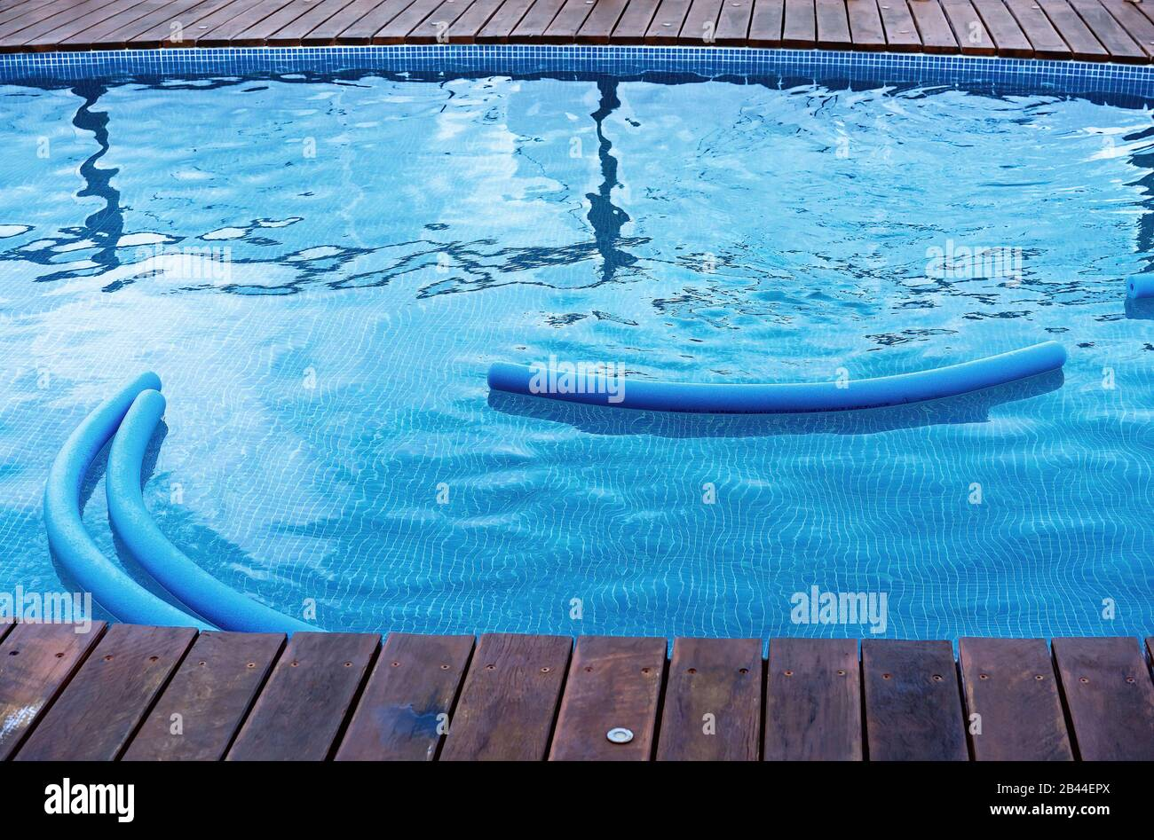 Blue pool floatation devices in a blue water pool edged with blue tiles and a timber deck Stock Photo
