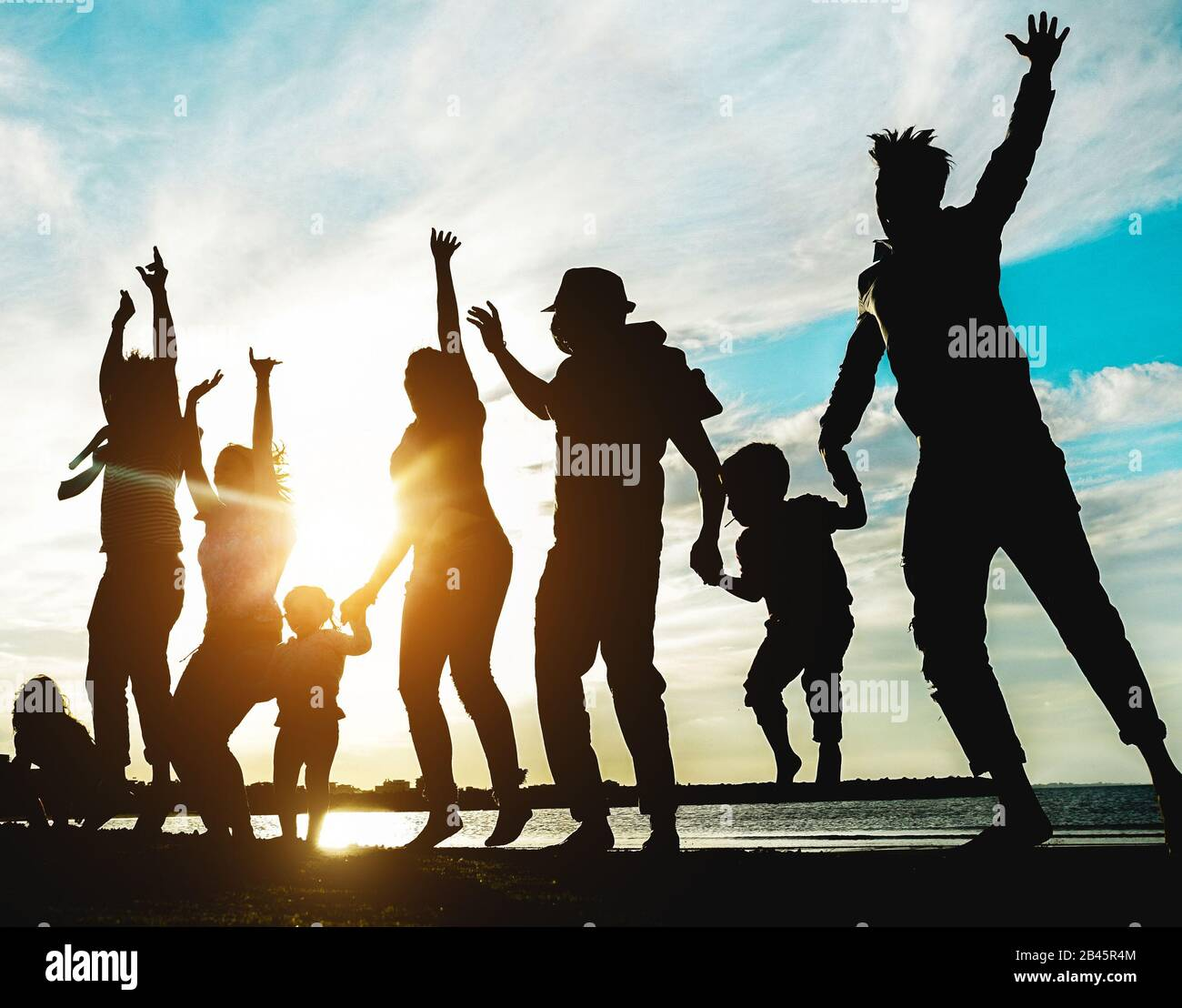 Silhouette of big family having fun on the beach at sunset - Father, mother, children and uncles enjoying time together - Focus on bodies - Love, rela Stock Photo