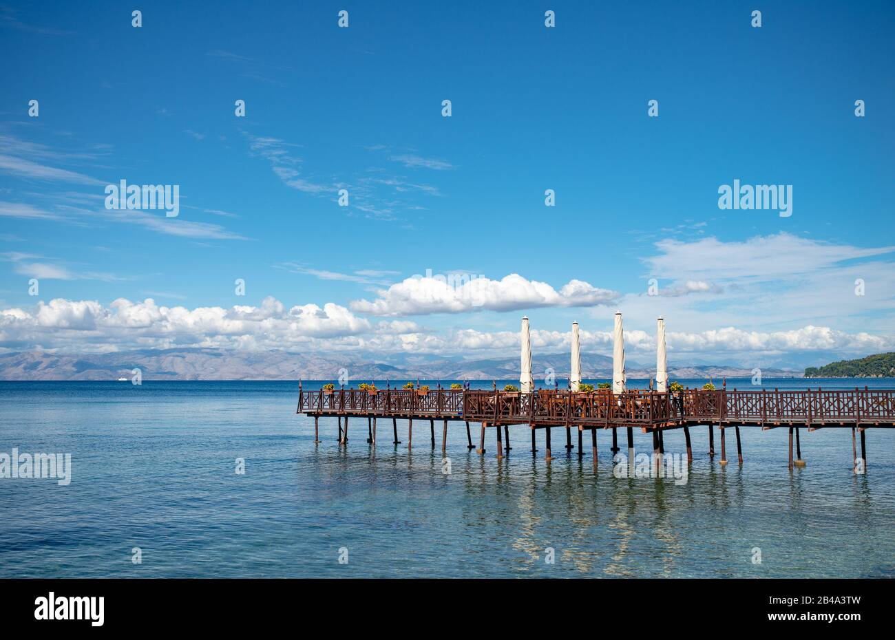 Long wooden pier with romantic cafe in end in Ionian sea. Greece. Beautiful lanscape, mountains on sealine. Sunny day with clouds on Corfu island. Stock Photo